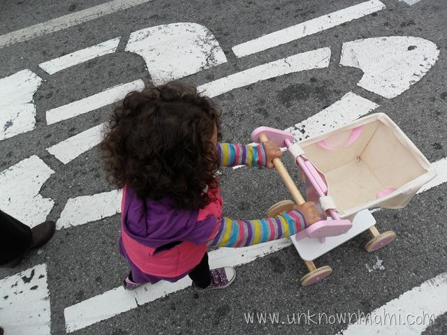 Little girl pushing shopping cart on street