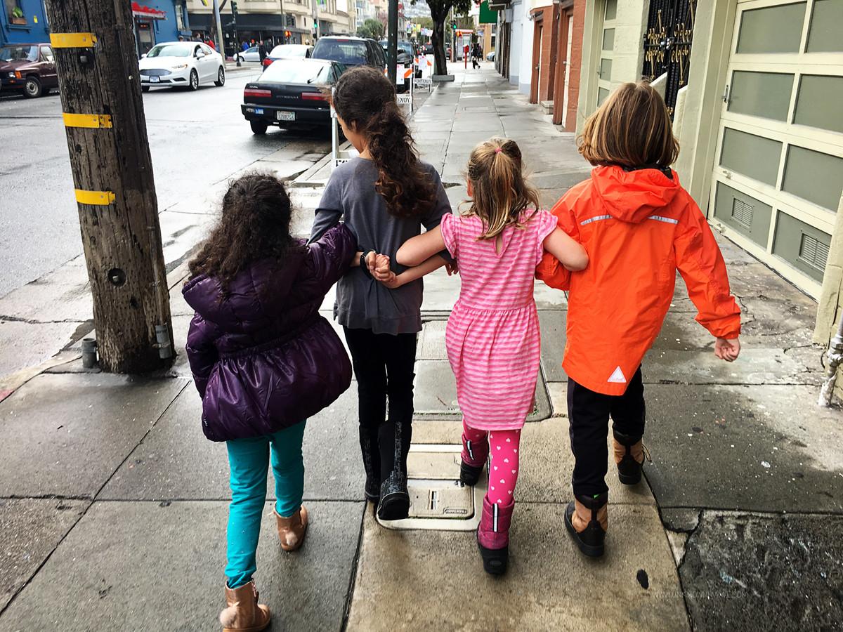 Little girls walking arm in arm