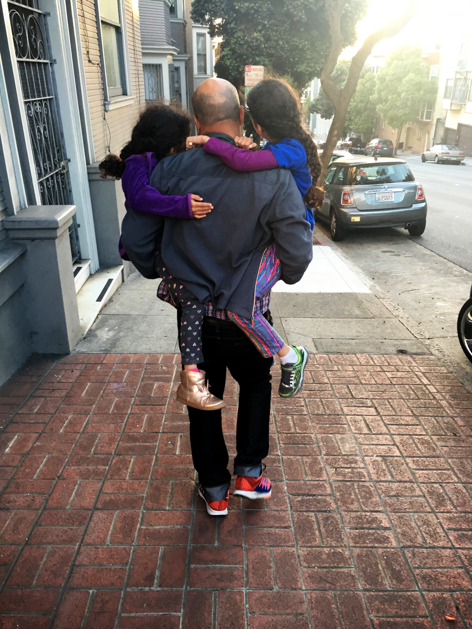 Father carrying daughters